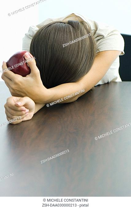 Teen girl holding apple, head resting on arms