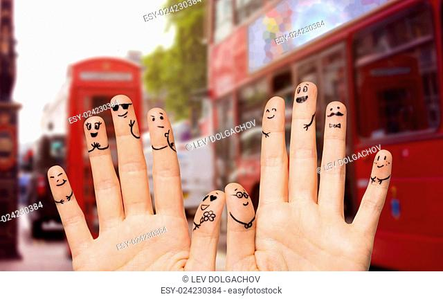 family, wedding, marriage, people and body parts concept - close up of two hands showing fingers with smiley faces over london city street and red bus...