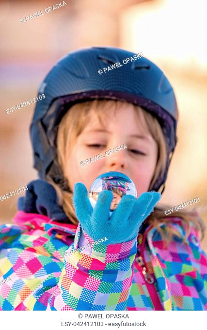 Winter portrait of a little girl wearing ski helmet and holding small glass ball with her own reflection