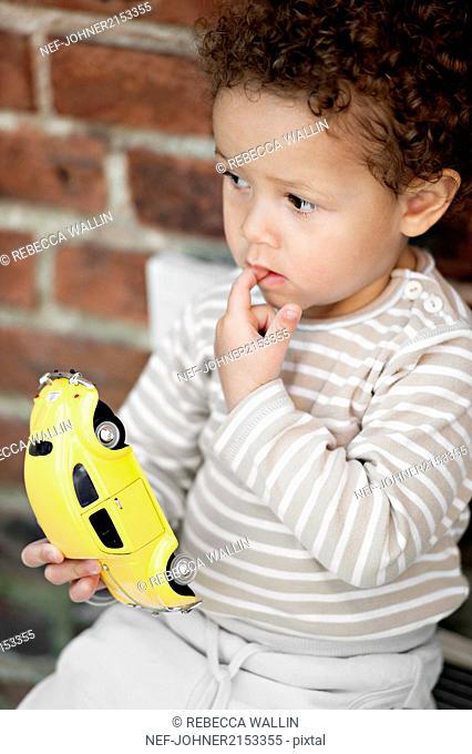 Little boy holding toy car