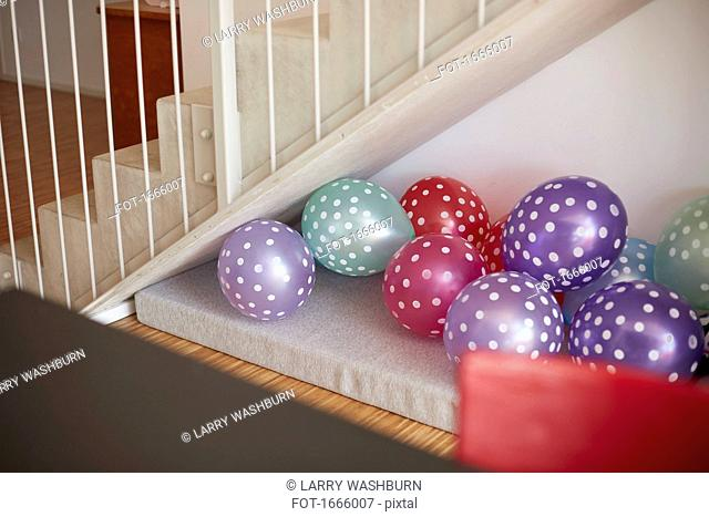Multi colored balloons against wall by staircase at home
