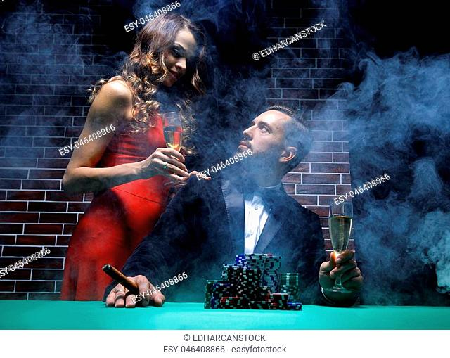 Man losing at poker table with woman comforting him in casino