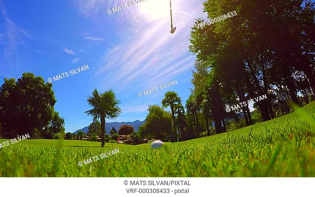 Golfer Making a Golf Swing in Backlit and Hitting the Golf Ball on the Grass in Ticino, Switzerland