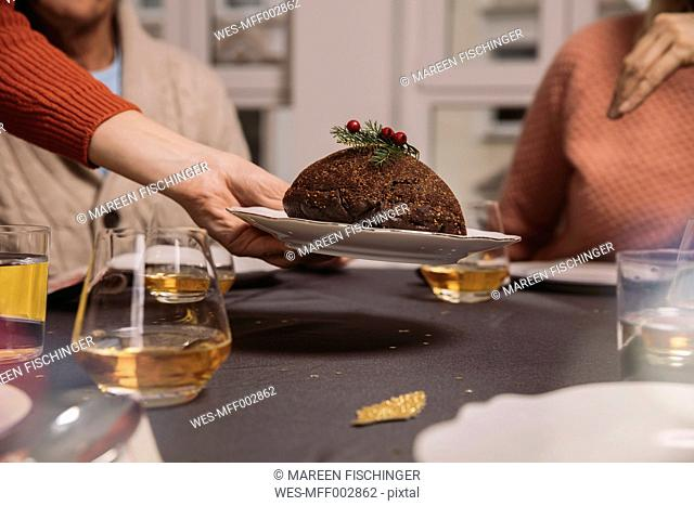 Close-up of Christmas pudding being put on table