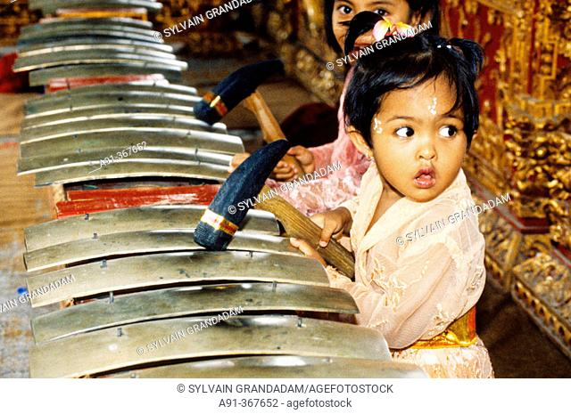 Child playing music at a gamelan (orchestra) Hinduist religious ceremony (odalan) in the Celuk Temple. Bali island. Indonesia