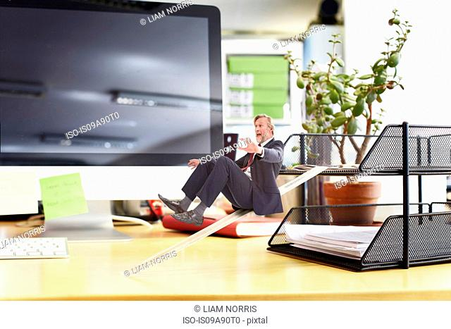 Mature businessman sliding down ruler on oversized desk