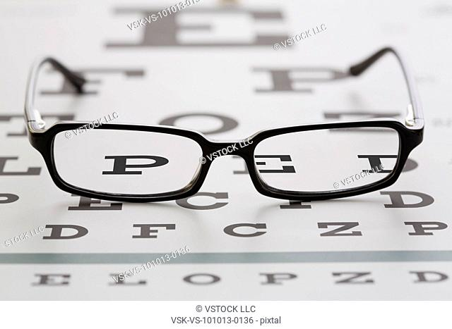 Spectacles lying on eye chart