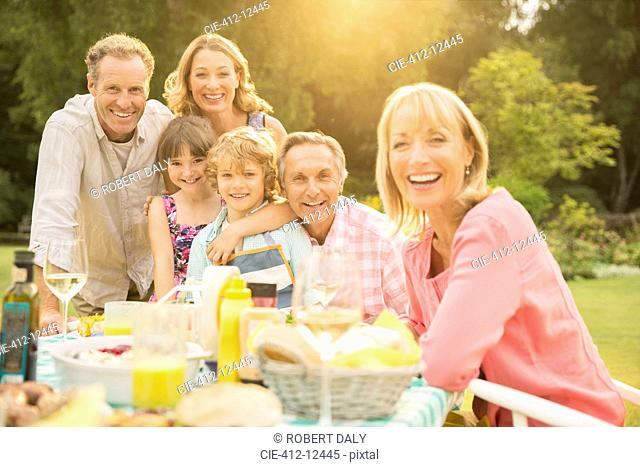 Multi-generation family at table in backyard