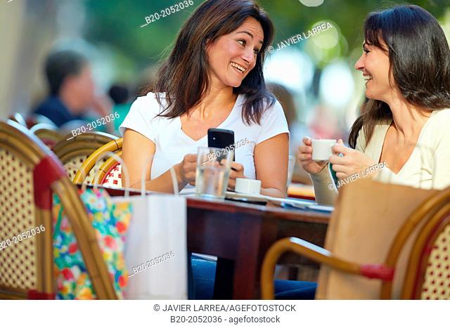 Looking a smartphone. Women sisters 35 and 40 years taking coffee on a terrace. Donostia. San Sebastian. Gipuzkoa. Basque Country- Spain