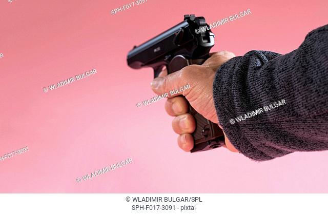 Person holding handgun against a pink background