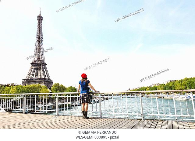 France, Paris, back view of woman wearing red beret looking at Eiffel Tower