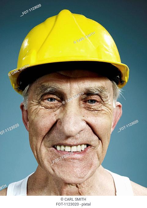 Headshot of a senior man wearing a yellow hardhat