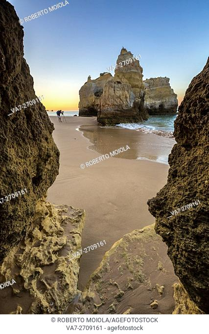 Photographer in action close to the cliffs and ocean at dawn Praia da Rocha Portimao Faro district Algarve Portugal Europe