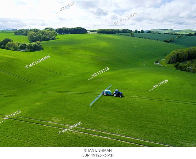 Aerial view of tractor spraying crop in green farm fields with pesticide