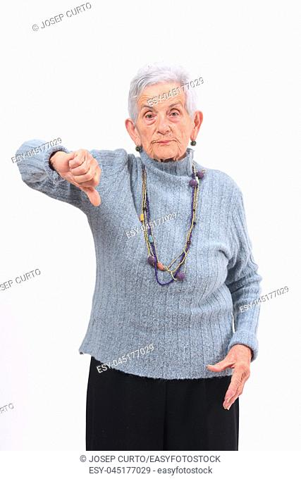 older woman holding her thumb down and serious on white background