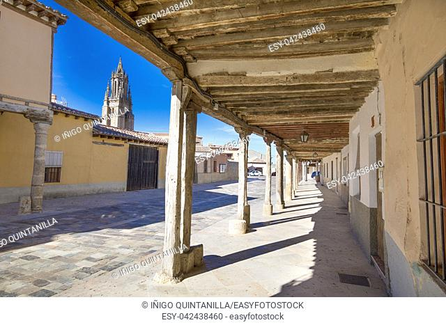 arcaded buildings, in medieval street, landmark and monument from seventeenth century, and church tower, in Ampudia village, Palencia, Castile Leon, Spain