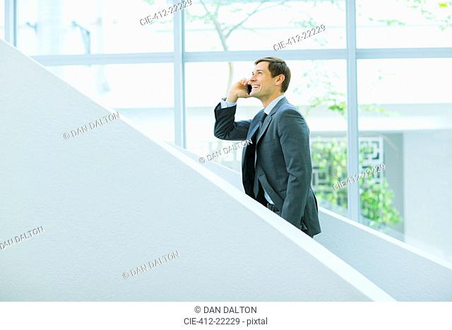 Businessman talking on cell phone on stairs of office building