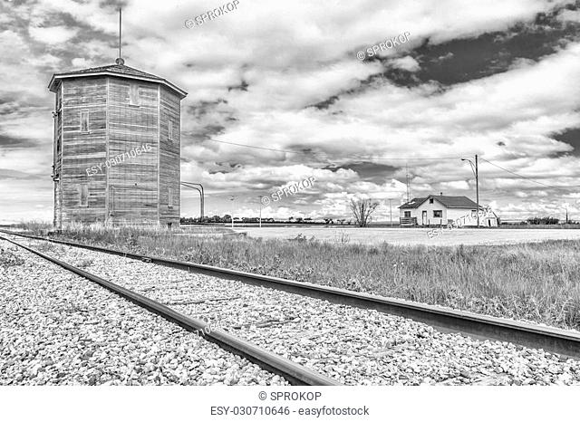 Old water tower or station along the railroad track near an old abandoned house on the prairies. Processed in black and white
