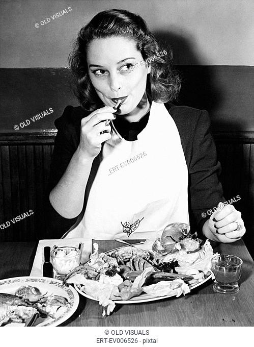 Young woman with a bib eating Lobster All persons depicted are not longer living and no estate exists Supplier warranties that there will be no model release...