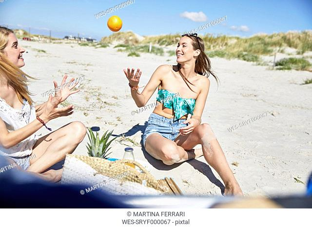 Two female friends on the beach throwing an orange