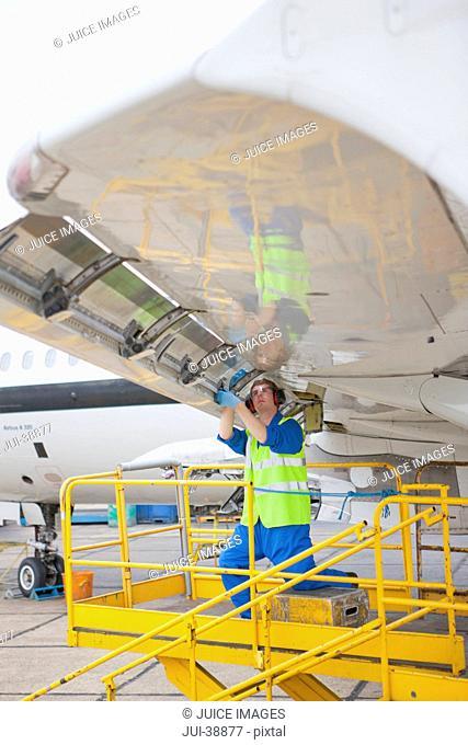 Engineer repairing flap on wing of passenger jet in hangar