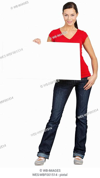 Portrait of young woman holding poster, smiling