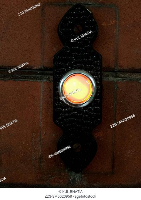 An illuminated doorbell button outside a house, Ontario, Canada