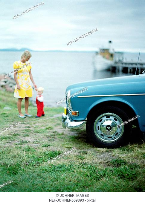 Mother and child by an old car, Sweden