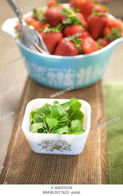Bowls of fresh herbs and strawberries
