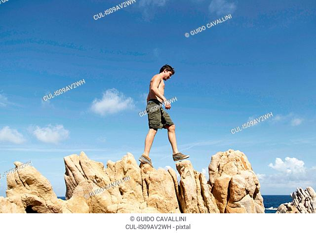 Low angle side view of young man climbing on rocks, Costa Paradiso, Sardinia, Italy