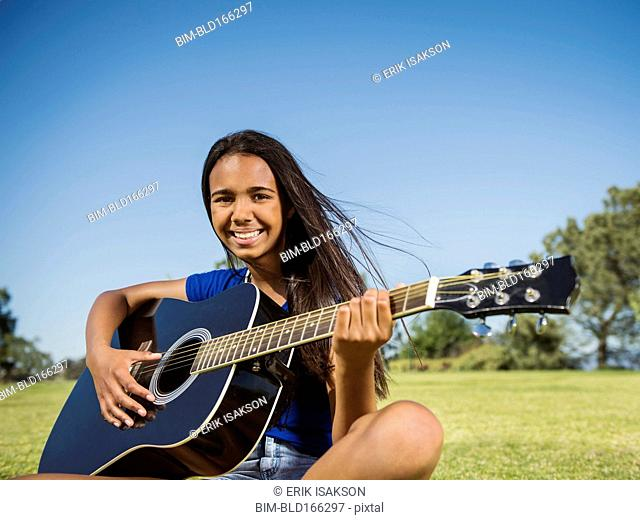 Mixed race girl playing guitar in park