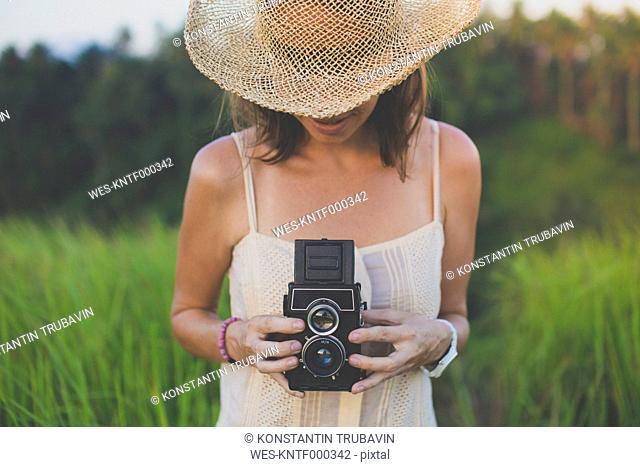 Woman with old camera in fields