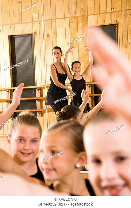 Portrait of ballet dancers 8-9 practicing while teacher instructing in dance studio with mirror in background