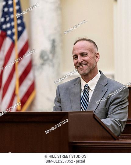 Smiling Caucasian politician at podium