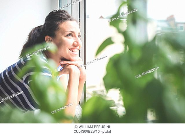 Happy young woman looking through apartment window