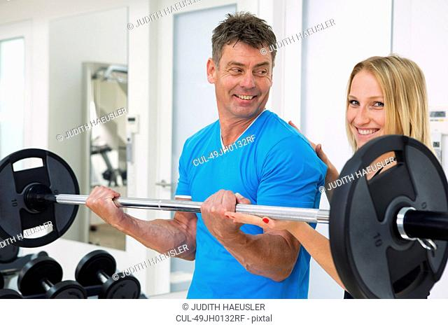 Trainer adjusting man's form in gym