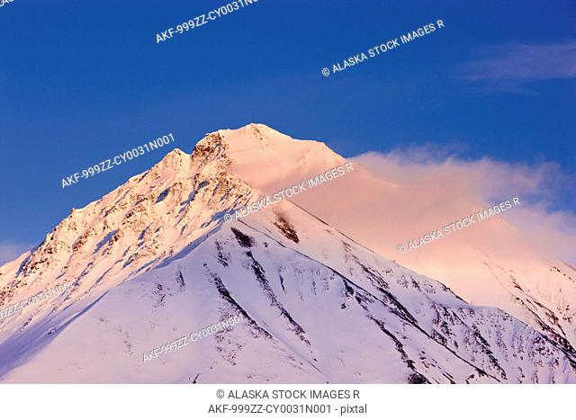 View of sunset alpenglow on the foothills of the Alaska Range in Broad Pass, Southcentral Alaska, Winter