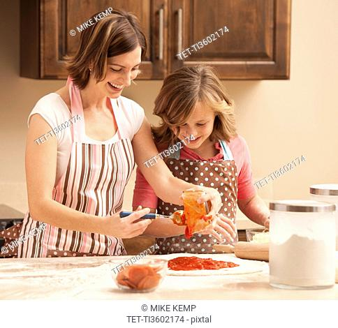 Mother and daughter 10-11 preparing pizza in kitchen