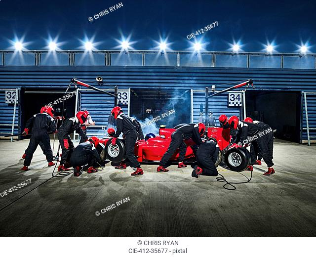 Pit crew working on formula one race car in pit stop