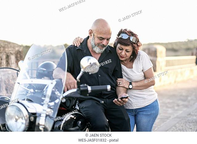 Spain, Jaen, mature couple with motorcycle with a sidecar looking at cell phone