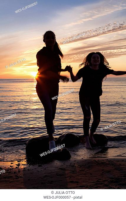 Germany, Ruegen, Two young female friends on the beach at sunset