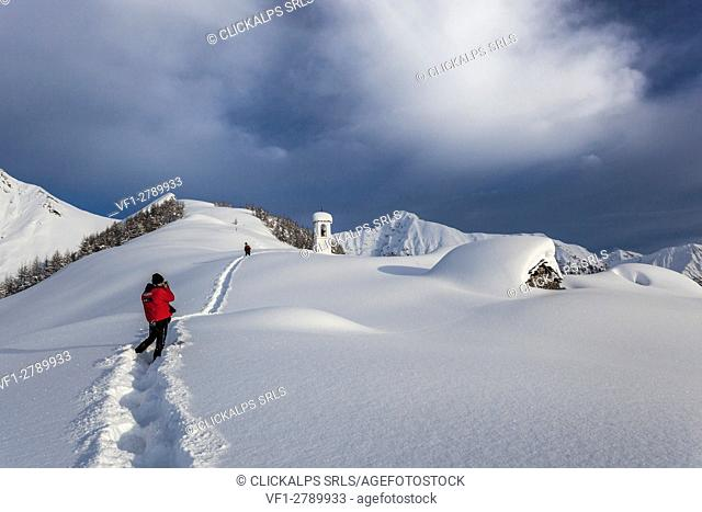 Italy, Italian Alps, Lombardy, The huts and the bell tower of Alpe Cima sorrounded by metres of snow