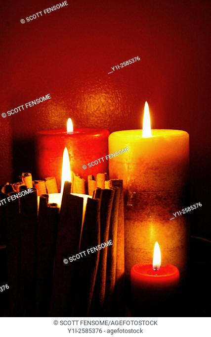 Brown-banded and red-banded pillar candles with cinnamon sticks
