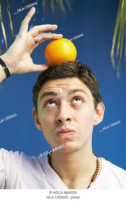 Young man balancing an orange on his head