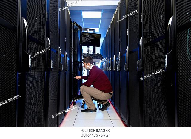 Technician, plugging in computer, working on server rack in data center