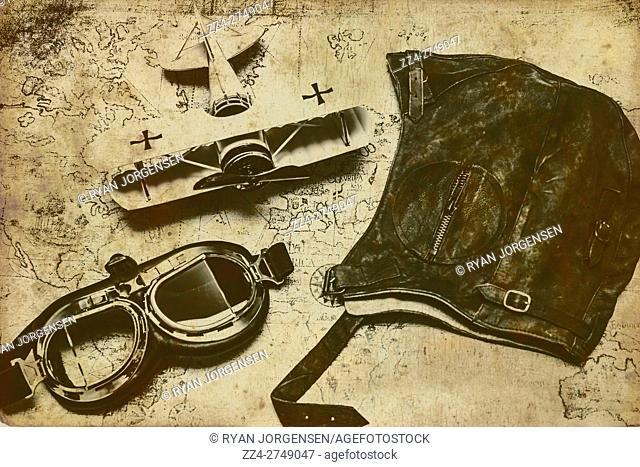 Adventure and travel in early aviation theme with goggles, pouch and model biplane on map