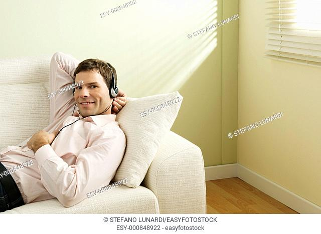 Young man listening to music on the couch