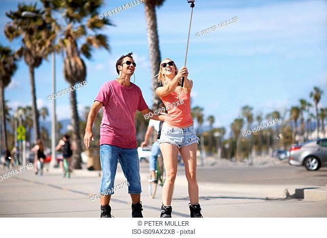 Couple rollerblading outdoors, taking self portrait, using selfie stick