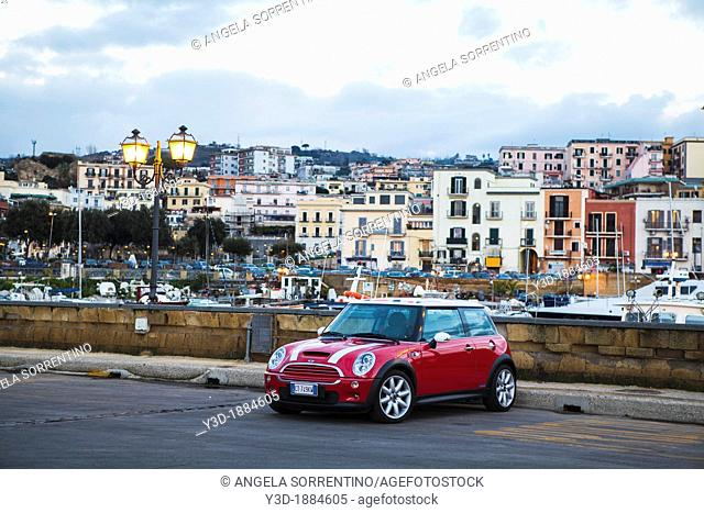 Bmw mini car parked in italian small town closed to the harbor, Naples, Italy