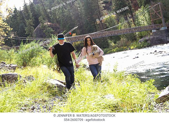 A young couple fishing with their dog and walking by the Spokane River, Spokane, Washington, USA